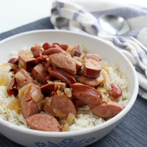 Bowl of red beans and rice on blue place mat with striped towel and spoon
