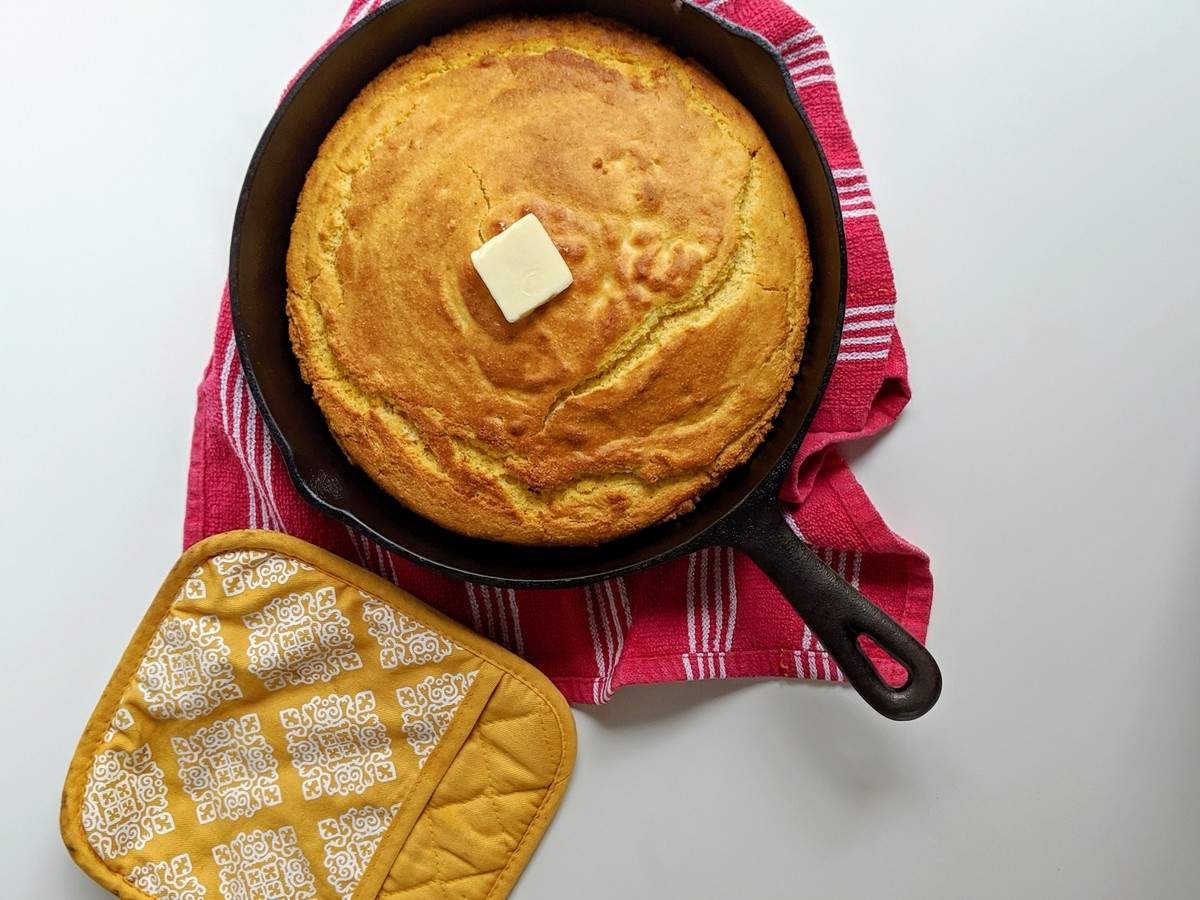 Cornbread in cast iron skillet with butter and pot holder