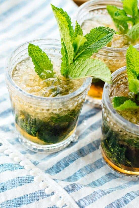 Mint Julep in short glass on blue striped towel with mint garnish