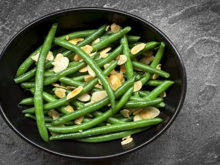 Green beans with toasted almonds, in black bowl over dark slate. Overhead view.