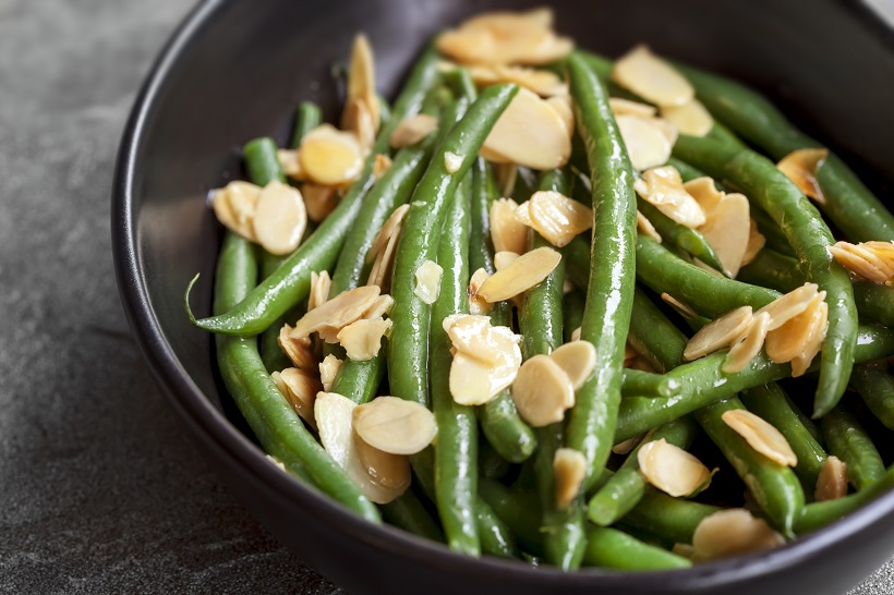 Green beans with toasted almonds, in black bowl over dark slate.