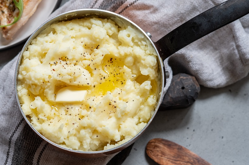 Mashed potato with spoon, in a copper pot
