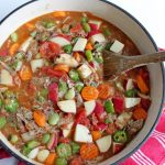 Vegetable soup with wooden spoon in dutch oven