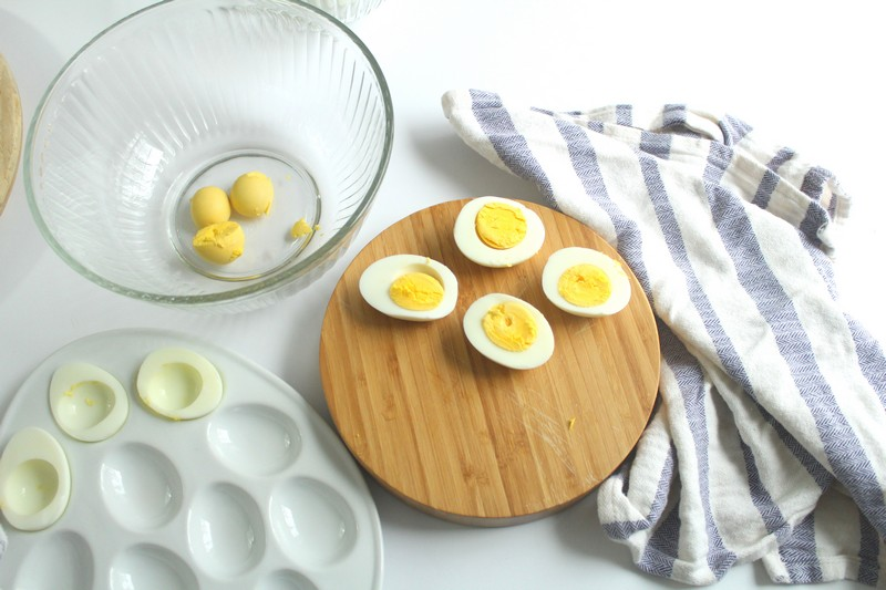 hard boiled eggs next to a bowl of a few egg yolks in process shot