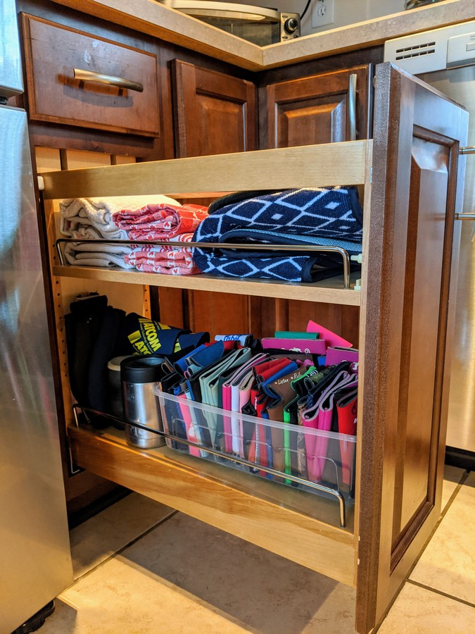 Dishtowels and drink koozies stored in rev a shelf pull out cabinet