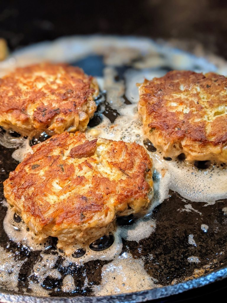 Three crab cakes cooking in a cast iron skillet