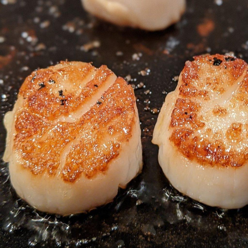 Two seared scallops on cast iron pan