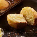 Corn muffin split in half with butter