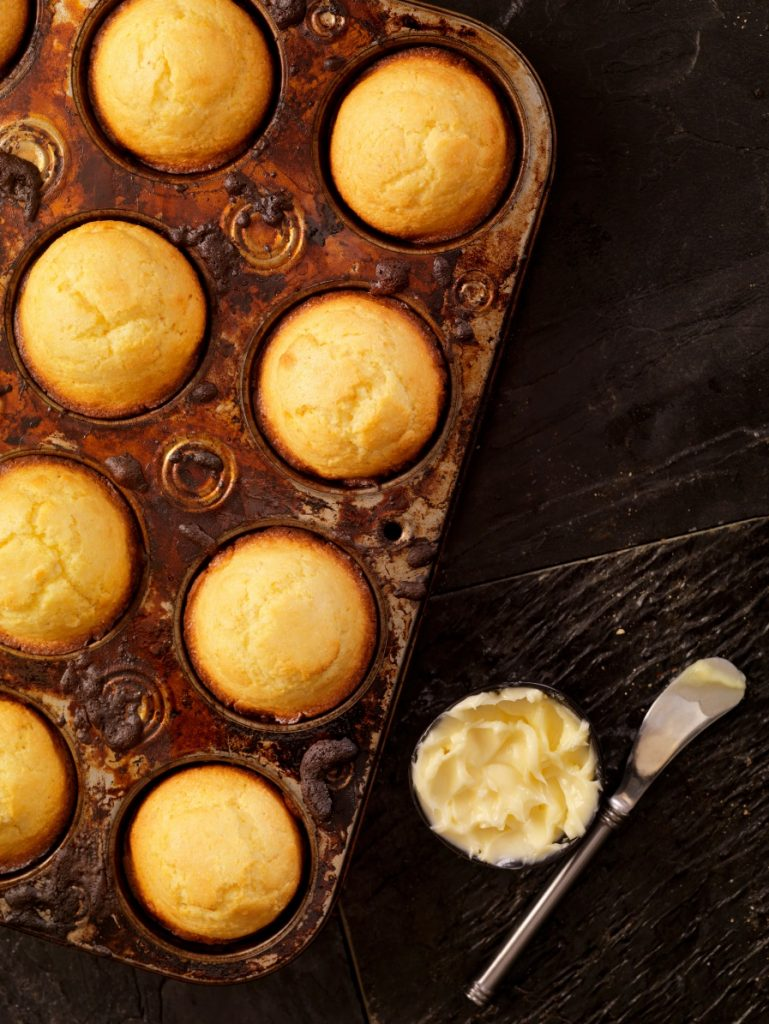 Corn muffins in baking tin with cup of butter on dark background