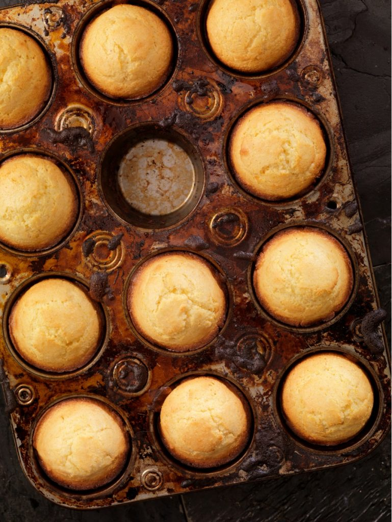 Muffin tin of corn muffins with one missing from middle