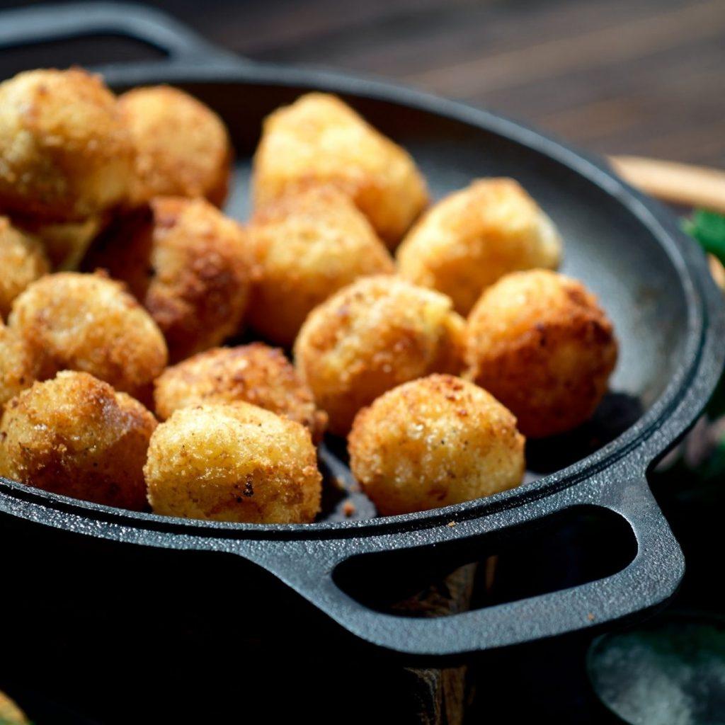 Potato croquettes in a black iron skillet