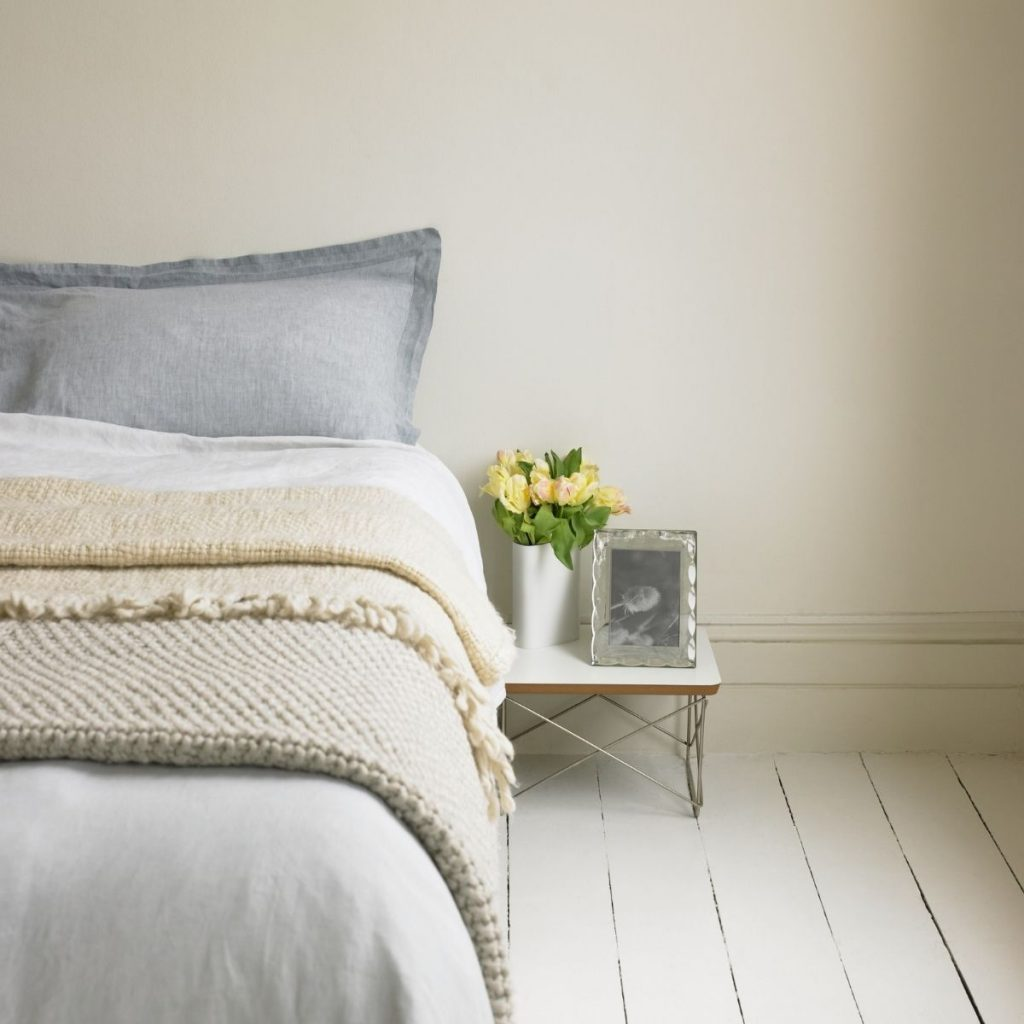 gray bed in beige bedroom with small nightstand