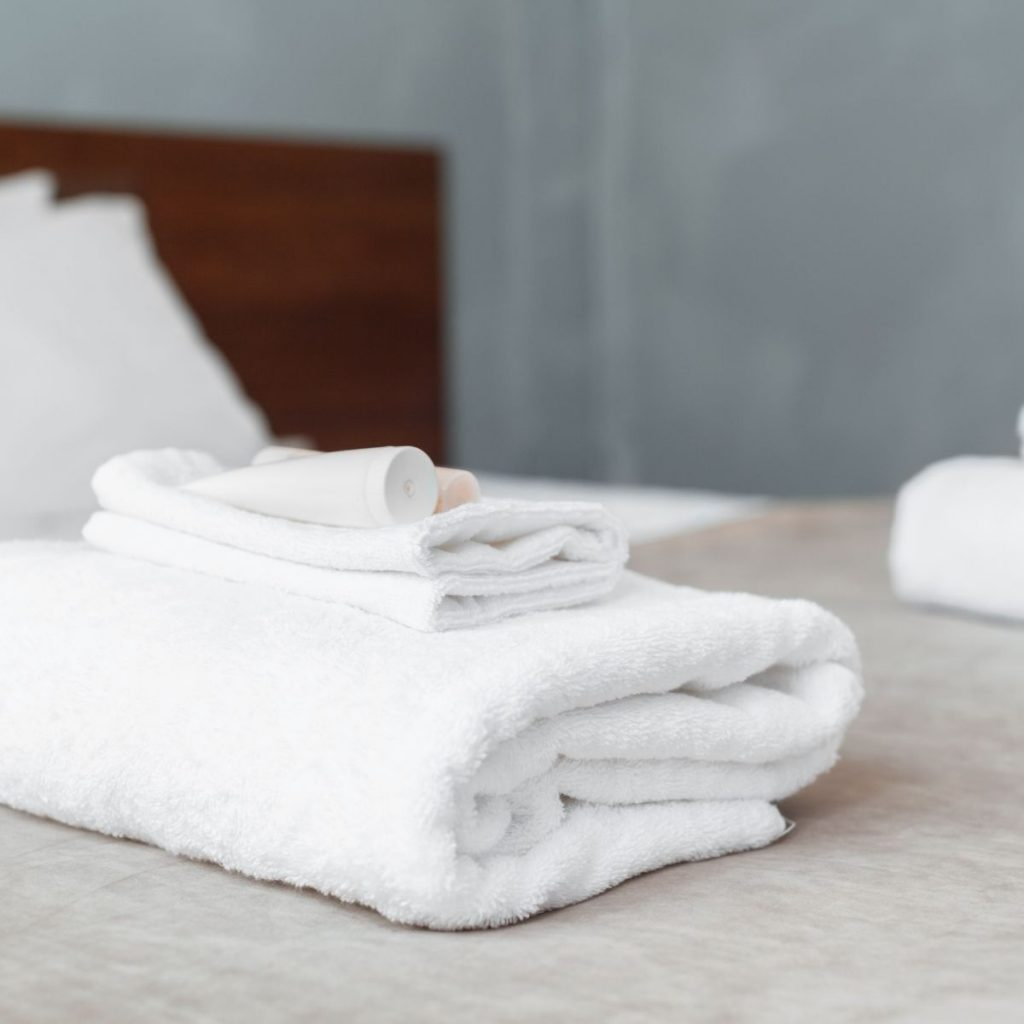 white towels folded on guest bed