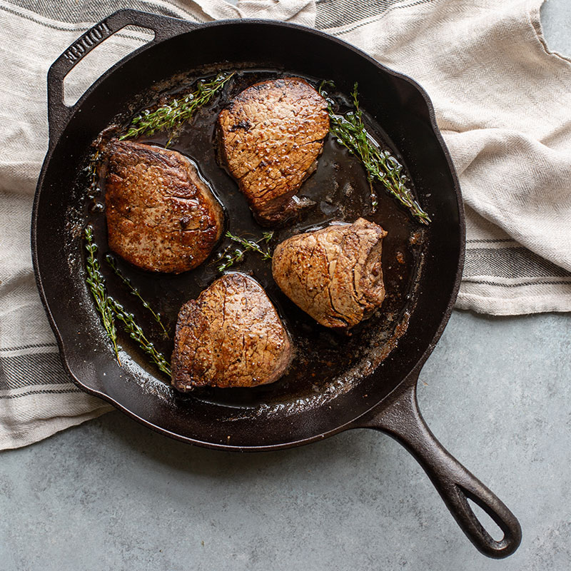 Cast iron pan with 4 steaks