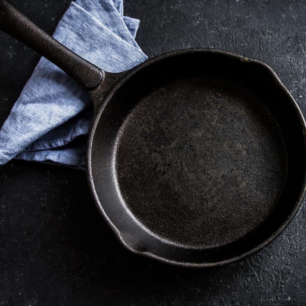 Cast iron skillet on dark background with blue towel