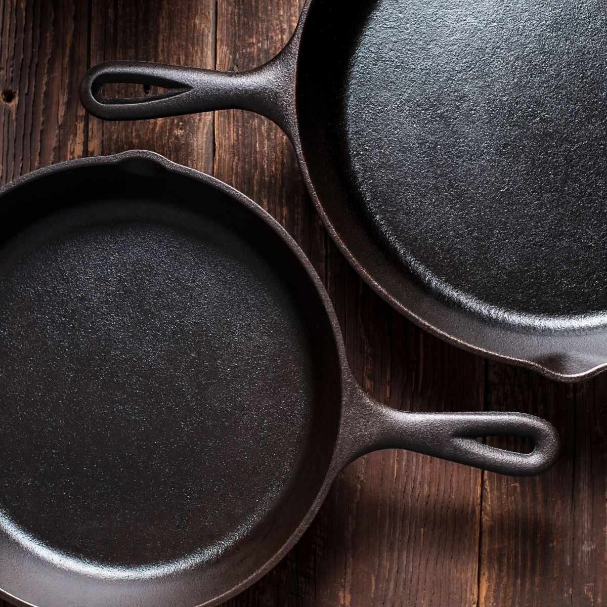 Two cast iron skillets on wooden background