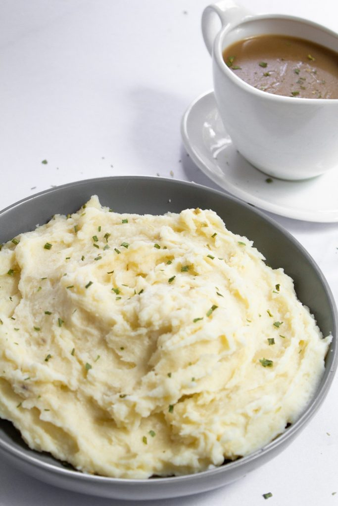 mashed potatoes garnished with chives and gravy in the background