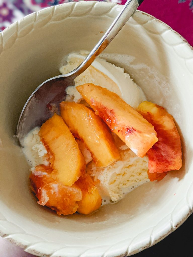 bowl of peaches over vanilla ice cream