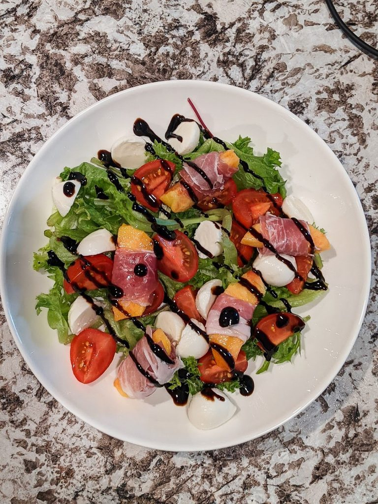 green salad with peaches, tomatoes, and mozzarella balls with balsamic glaze drizzled over ingredients in white bowl